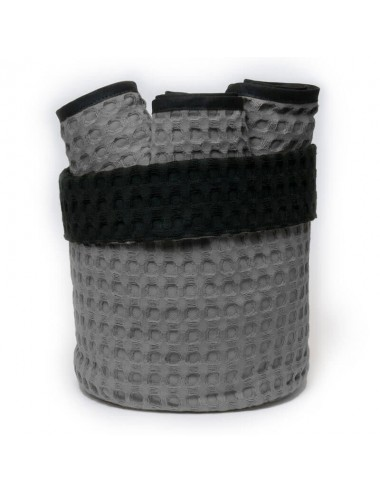 Small, round basket made of sand-colored waffle weave with interior in black waffle weave and washcloths