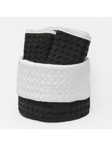 Small, round basket made of black waffle weave with interior in white waffle weave and washcloths