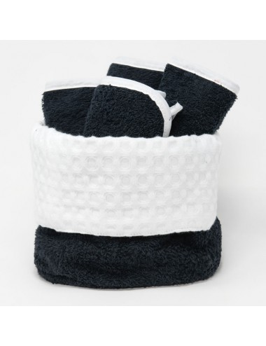 Small, round basket in black terry cloth with the interior in white waffle weave, and washcloths